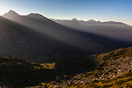 Sunbeams throught the mountain ridge to the valley