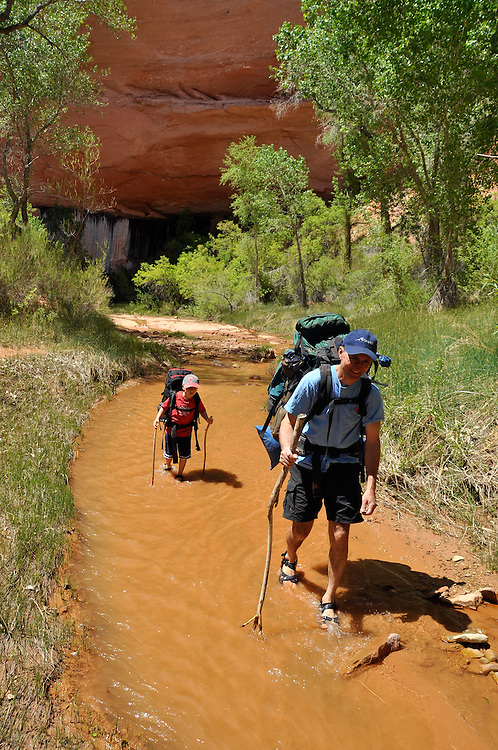 Father and son backpacking in Coyote Gulch, a tributary of the Escalante River in Southern Utah.