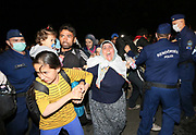 Migrants clash with police close to the Hungarian and Serbian border town of Roszke, Hungary, September 8 2015. The UN's humanitarian agencies are on the verge of bankruptcy and unable to meet the basic needs of millions of people because of the size of the refugee crisis in the Middle East, Africa and Europe, senior figures within the UN have told the media.