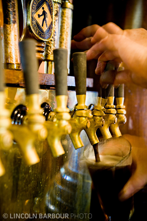 A close up view of bartender's hands filling a pint from a row of taps fixed to the wall.  They look old and warn.