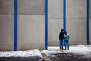 Street scene in the city of Ostrava, two boys in front of a wall protecting the inhabitants of a neighbourhood of sound coming from a close by city highway.