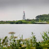 Nederland, Amsterdam , 27 juli 2011..Vuurtoreneiland bij Durgerdam..IJdoorn - Voor wie al langer droomt van een eigen eiland met een heuse eigen vuurtoren, dan is er wellicht nu een kans om deze droom te verwezenlijken.?.Staatsbosbeheer is namelijk op zoek naar een nieuwe beheerder voor het Vuurtoreneiland. Het eiland ligt in het IJmeer net uit de kust van de polder IJdoorn bij Durgerdam. .Het fort is wel vervallen en de kosten voor restauratie bedragen tussen de 1 en 3 miljoen euro. Er zijn volgens Staatsbosbeheer wel subsidiemogelijkheden voor een deel van deze kosten. .Vuurtoreneiland is nog geen twee voetbalvelden groot. Er staat een kleine vuurtoren op. Samen met Pampus en Fort Diemerdam verdedigde dit stipje in het IJmeer ooit de mond van het IJ en de hoofdstad tegen aanvallen over de Zuiderzee. Op het Vuurtoreneiland staat namelijk één van de 45 forten die samen de Stelling van Amsterdam vormen. De stelling is sinds 1996 UNESCO werelderfgoed..Vuurtoreneiland (Lighthouse Isle) near Amsterdam is for rent. It has to be renovated (!-3 million) and is part of the Defence Line of Amsterdam, on the Unesco World Heritage List since 1996.