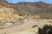 Person cycling in Cabo de Gata national park, Monsul, near San José, Almeria, Spain