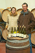 Vincent Paris, owner and wine maker and his wife in front of a barrel with wine bottles with tasting samples.  Vincent Paris, Cornas, Ardeche, Ardèche, France, Europe