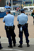 Two police officers outside Sydney Olympic Stadium, one using his utility belt to carry a bottle of water. Sydney, Australia