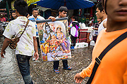 "24 AUGUST 2013 - BANGKOK, THAILAND:     A man tries to sell a painting of Hindu deities Shiva, Ganesha and Parvati on a street in Bangkok. Thailand entered a ""technical"" recession this month after the economy shrank by 0.3% in the second quarter of the year. The 0.3% contraction in gross domestic product between April and June followed a previous fall of 1.7% during the first quarter of 2013. The contraction is being blamed on a drop in demand for exports, a drop in domestic demand and a loss of consumer confidence. At the same time, the value of the Thai Baht against the US Dollar has dropped significantly, from a high of about 28Baht to $1 in April to 32THB to 1USD in August.   PHOTO BY JACK KURTZ"