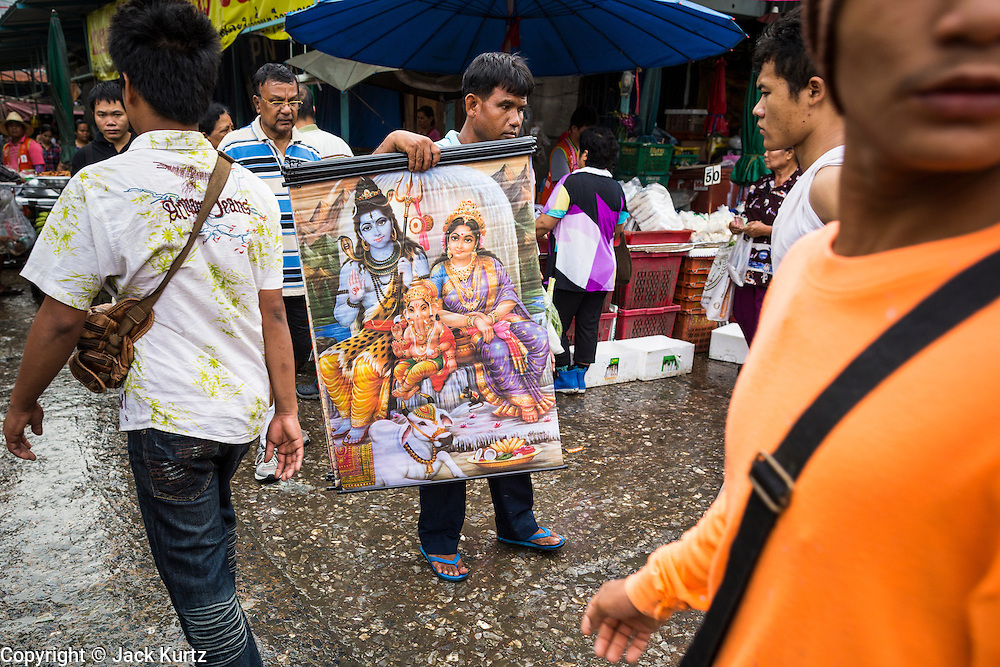 """24 AUGUST 2013 - BANGKOK, THAILAND:     A man tries to sell a painting of Hindu deities Shiva, Ganesha and Parvati on a street in Bangkok. Thailand entered a """"technical"""" recession this month after the economy shrank by 0.3% in the second quarter of the year. The 0.3% contraction in gross domestic product between April and June followed a previous fall of 1.7% during the first quarter of 2013. The contraction is being blamed on a drop in demand for exports, a drop in domestic demand and a loss of consumer confidence. At the same time, the value of the Thai Baht against the US Dollar has dropped significantly, from a high of about 28Baht to $1 in April to 32THB to 1USD in August.   PHOTO BY JACK KURTZ"""