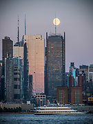 The moon shines over the Hudson Yards modern building complex in New York City harbor.
