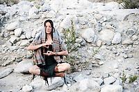 Woman Wild Woman meditating in desert wilderness nature.