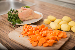 Cut carrots, peeled potatoes, raw chicken with parsley at kitchen counter, Munich, Bavaria, Germany
