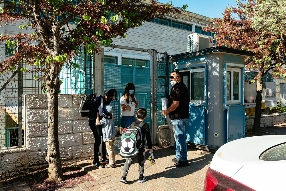 Israeli pupils and their parents, are seen as they await their turn to enter the elementary school where the girls study, in Jerusalem, Israel, on May 3, 2020.
