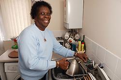 Elderly woman filling a kettle,