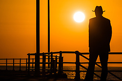 © Licensed to London News Pictures. 10/04/2019. Aberystwyth, UK. At the end of a day unbroken blue skies and warm spring sunshine, the sun sets spectacularly behind the silhouettes of people walking among the promenade in Aberystwyth on the Cardigan Bay coast of west Wales. Credit : Keith Morris/LNP