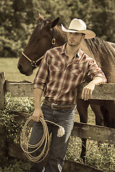 cowboy leaning against a fence with a horse