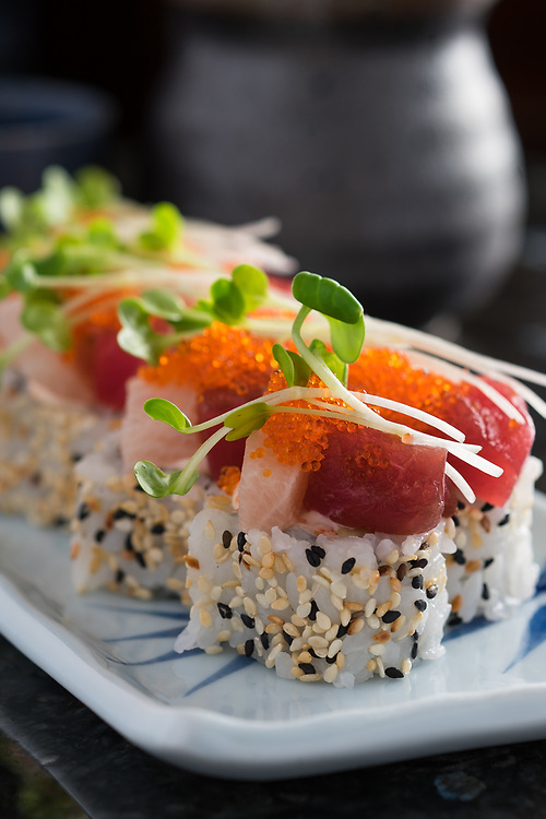 Fresh sushi rolled in sesame seed and topped with greens<br /> <br /> [Sakura 15_02_014]