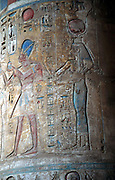 Goddess Isis with King Tuthmosis III (15th century BC) at Deir el Bahn, Luxor, Egypt. Painted limestone relief.  Isis principal goddess of Egypt shown with horns and solar disc on head.