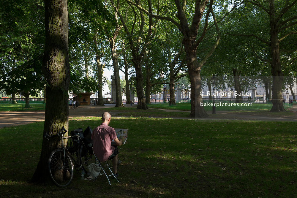 With a further 184 reported UK Covid deaths in the last 24 hrs, a total now of 43,414, an artist creates art with Buckingham Palace in Green Park within view during the last stages of the pandemic, on 26th June 2020, in London, England. Many have found lockdown as an opportiunity to be more creatively active and closer to the natural world. Government restrictions on the 2 metre rule is to be realxed on 4th July and replaced with 'one metre plus' in the hope it stimulates the struggling UK economy.