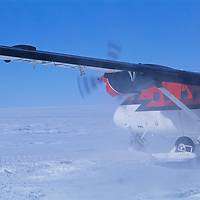 A Twin Otter ski plane lands in the Queen Maud Mountains of Antarctica - part of the Trans-Antarctic range.
