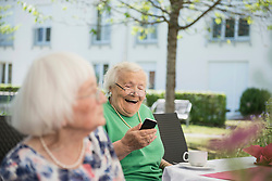 Senior woman laughing and using smartphone, Bavaria, Germany