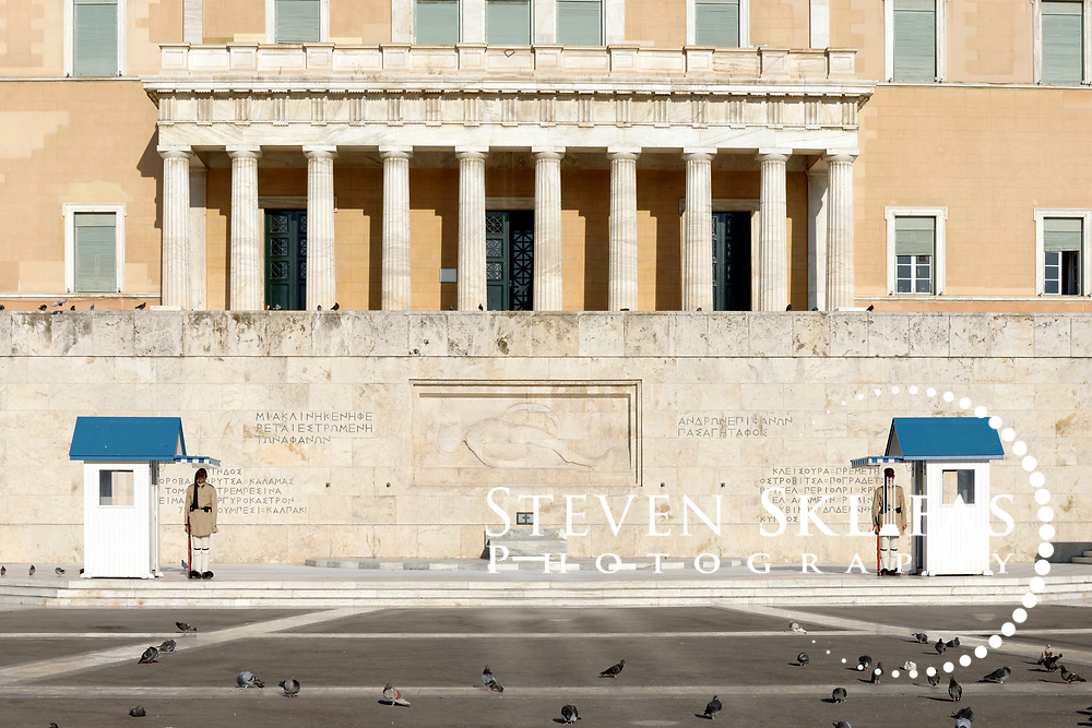 Syntagma square. Athens. Greece. View of two elite members of the Presidential ceremonial guard unit known as Evzones standing guard in front of the monument to the Unknown Soldier. Located in front of the Greek Parliament, The monument to the Unknown Soldier, erected in 1929-1932, depicts a relief of a dying Greek solider and is watched around the clock by a pair of Evzones standing motionless outside their sentry boxes wearing traditional dress. These guards are wearing the summer uniform tunic that is light khaki in colour.