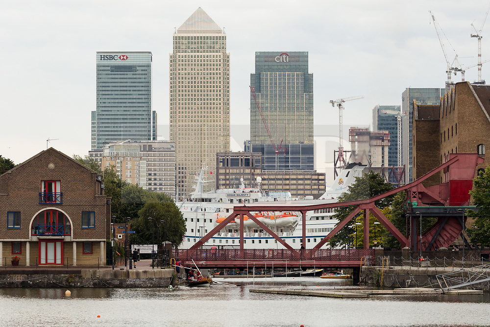 © Licensed to London News Pictures. 14/08/2017. LONDON, UK.  The large cruise ship, Ocean Majesty leaves London on the River Thames this evening, passing a residential area in east London and in front of the Canary Wharf skyscrapers. Ocean Majesty is approximately 445m long and carries up to 621 people. Environmentalists claim thepollutioncreated by giantcruise ships travelling into the capital city outweigh their economic benefits. The Port of London Authority (PLA) are conducting a work programme during 2017 to monitor air quality and pollution caused by river traffic on the River Thames.  Photo credit: Vickie Flores/LNP