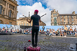 Edinburgh, Scotland, UK. 6th August  2021.  Images from the Royal Mile in Edinburgh Old Town on the opening day of the Edinburgh Fringe Festival 2021.  The festival looks very different from two years ago . Very few street performance spaces are permitted and far fewer tourists are evident. Also a high police visibility, there are more police officers than performers on the street, is in marked contrast to previous years. Pic; Performer entertains crowd in purpose built screened off outdoor performance space designed to limit audience capacity. Iain Masterton/Alamy Live news.