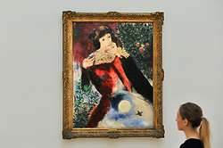 """© Licensed to London News Pictures. 06/10/2017. London, UK. A staff member views """"Les Amoureux"""", 1928, by Marc Chagall at a preview at Sotheby's in New Bond Street of contemporary, impressionist and modern art works to be auctioned in New York in November 2017 Photo credit : Stephen Chung/LNP"""