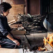 Inaba-san warming up in front of a fire before heading to sea. She is the last active Ama diver in Futo Harbor, Izu Peninsula, Japan.