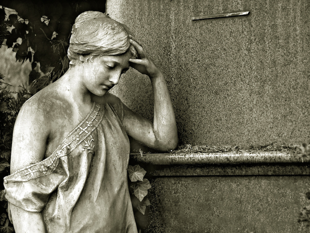 A thinking statue in a cemetary