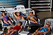 Passengers sunbathe and talk on the deck of the P&O liner Oriana