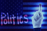 """A white gloved hand with a dirty index finger has spelled the work """"politics"""" in the dust covering an American flag.Black light"""