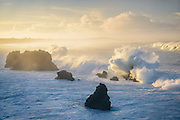 A large wave crashes over a rock along the Sonoma Coast after a winter storm. Bodega Bay, California