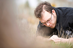 Back from the Brink Communications Manager James Harding-Morris attempting to lure a cricket from its burrow, part of Field cricket Gryllus campestris translocation project, RSPB Farnham Heath Nature Reserve, Surrey, April