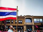 """29 APRIL 2017 - MINNEAPOLIS, MINNESOTA:  The opening parade, led by a man carrying the Thai flag, at Songkran Uptown. Several thousand people attended Songkran Uptown on Hennepin Ave in Minneapolis for the city's first celebration of Songkran, the traditional Thai New Year. Events included a Thai parade, a performance of the Ramakien (the Thai version of the Indian Ramayana), a """"Ladyboy"""" (drag queen) show, and Thai street food.    PHOTO BY JACK KURTZ"""