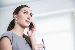 Businesswoman talking on mobile phone in an office, Munich, Bavaria, Germany