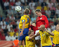Photo: Chris Ratcliffe.<br /> Sweden v England. FIFA World Cup 2006. 20/06/2006.<br /> Olof Melberg of Sweden clashes with Peter Crouch of England.