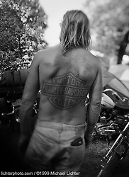 Harley Back Piece. Humboldt, IA. 1999<br /> <br /> Limited Edition Print from an edition of 50. Photo ©1999 Michael Lichter.<br /> <br /> The Story: Its unique - the Harley logo tattooed on arms, backs, tops of heads, and sensitive areas that don't see the light of day. It's displayed like a badge of honor and seen as an exclusive club membership. There's a loyalty and pride of ownership that has brand managers at other companies green with envy.