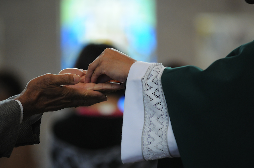 Communion is distributed during a mass at St. Eulalia Catholic Church in Maywood.