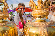 06 JANUARY 2013 - BANGKOK, THAILAND:  Women ring prayer bells in Sanam Luang during a prayer service for a relic of the Buddha's hair in Bangkok. The relic has been on display in Bangkok for about 10 years. There was a ceremony in Sanam Luang in Bangkok Sunday to honor the relic. People prayed for it and received blessings from Buddhist monks and Brahmin priests who presided over the service. The hair is being moved to Ayutthaya, where it will be displayed in a Buddhist temple. The piece of hair has been on loan to Thai Buddhists from a Buddhist temple in Sri Lanka.   PHOTO BY JACK KURTZ