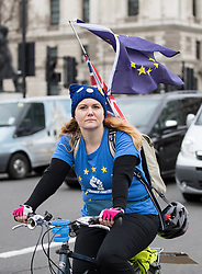 © Licensed to London News Pictures. 29/03/2017. London, UK. A woman cycles around Parliament Square with EU flags on her back, before British Prime Minister Theresa May arrives at Parliament, where the Prime Minister will deliver article 50 today. Photo credit : Tom Nicholson/LNP
