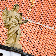 Statue in Prague Castle against terracotta roof tiles