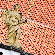 Statue in Prague Castle against terracotta roof tiles