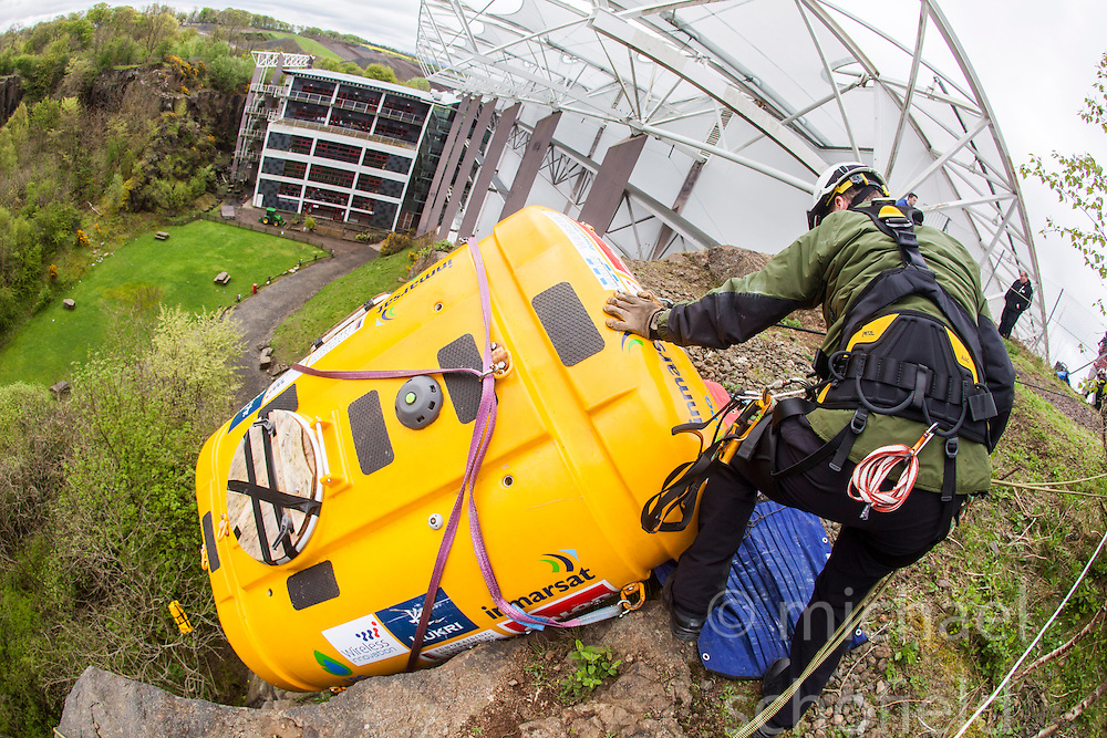 Stevie Young helping Nick Hancock getting in some winch practise with his Rock Pod, at the Edinburgh International Climbing Arena, for his 60 day Rockall Solo 2014 endurance expedition. Nick will use the Rock Pod, a modified plastic water tank, to live for two months on Rockall, a uninhabited remote granite islet, hundreds of miles off Scotland in the north Atlantic, in order to raise funds for Help for Heroes.