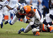 Denver Broncos running back C.J. Anderson (22) gets tackled by Indianapolis Colts inside linebacker D'Qwell Jackson (52) and a diving Indianapolis Colts cornerback Vontae Davis (21) on a first quarter run of 9 yards during the NFL week 19 AFC Divisional Playoff football game against the Indianapolis Colts on Sunday, Jan. 11, 2015 in Denver. The Colts won the game 24-13. ©Paul Anthony Spinelli