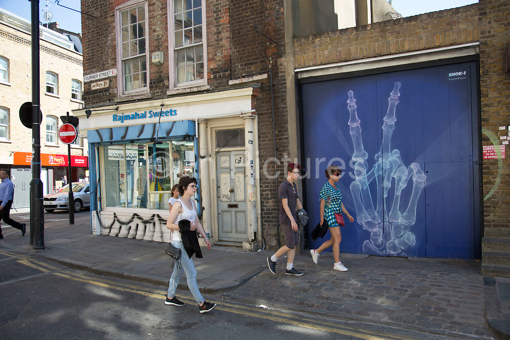 Street art x-ray hand giving the V sign by Shok-1 in the Brick Lane area of Shoreditch, East London, United Kingdom. Street art in the East End of London is an ever changing visual enigma, as the artworks constantly change, as councils clean some walls or new works go up in place of others. While some consider this vandalism or graffiti, these artworks are very popular among local people and visitors alike, as a sense of poignancy remains in the work, many of which have subtle messages.