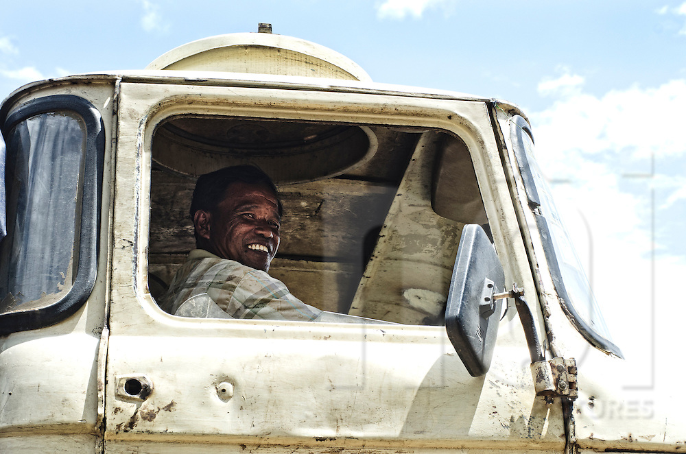 A Laos man truck driver drives with open windows and smile to the photographer. Sekong Province, Laos, Asia