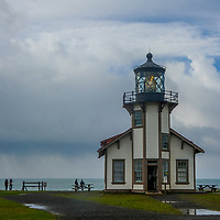 Visitors stand beside the Point Cabrillo Light Station near Pine Grove, California.