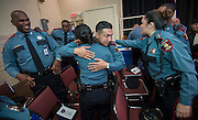 """Minhnguyet """"Nicky"""" Tran, center, gets a hug from a fellow officer after a swearing-in ceremony for new officers at the Houston ISD Police Department, March 3, 2014."""