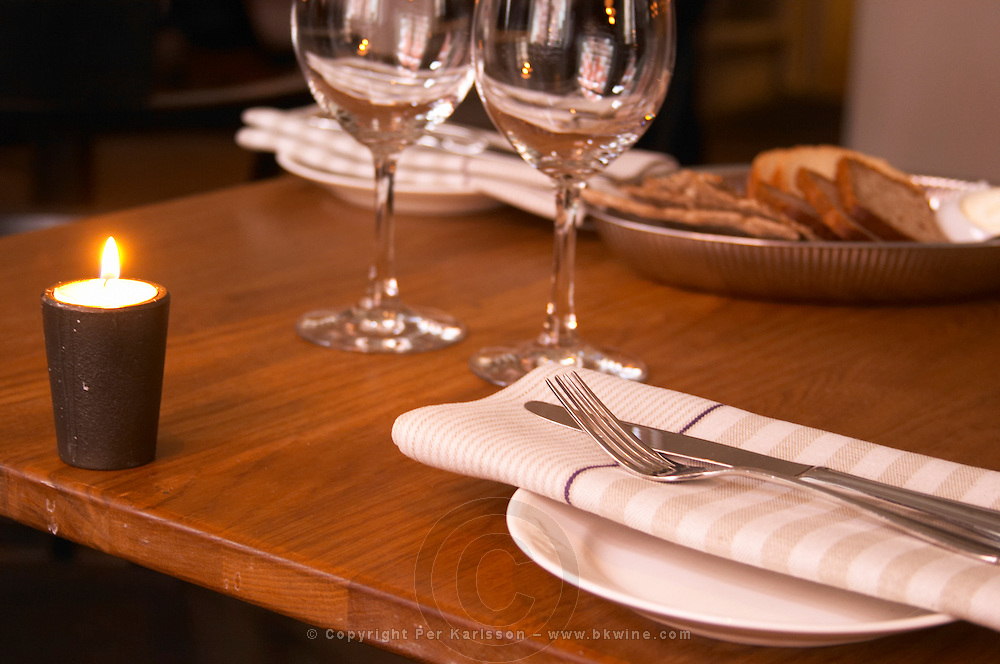 Detail of The interior of the restaurant Nalen with tables set for guests and a waiter waitress coming from the kitchen. wine glasses linen napkins cutlery Stockholm, Sweden, Sverige, Europe