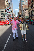 New York, NY - 25 June 2017. New York City Heritage of Pride March filled Fifth Avenue for hours with groups from the LGBT community and it's supporters.Two men, one playing an accordion, with a sign announcing that they have been together 41 years, and were married in 2003.